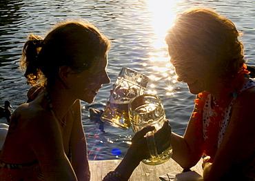 Young women toasting with beer steins, Seehaus Beergarden, English Garden, Munich, Bavaria, Germany