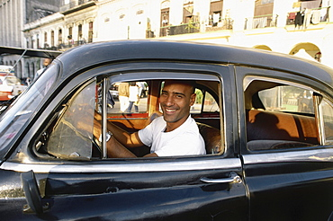 A man looking smiling out of a car, Prado, Havana, Cuba