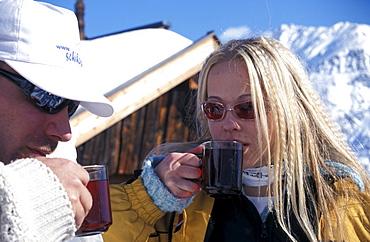 Couple having a warm drink at the Obstlerhuette, Soelden, Oetztal, Tyrol, Austria