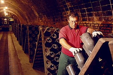 Man turning bottles, Cava Cellar methode champenoise, Codorniu, Sant Sadurni d'Anola, Catalonia, Spain
