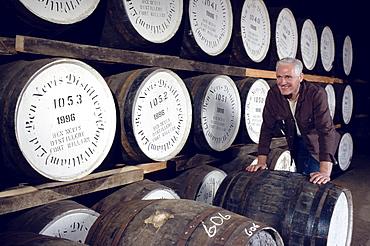 Man rolling barrels at Ben Nevis distillery, Fort William, Invernesshire, Scotland, Great Britain, Europe