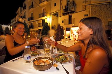 Two young women eating dinner in Restaurant La Oliva, Dalt Vila, Ibiza Stadt, Ibiza, Balearic Islands, Spain