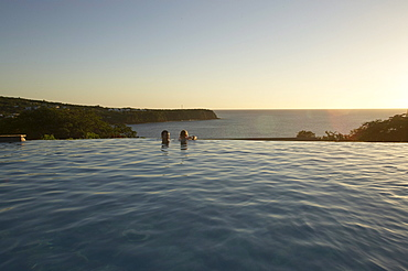 People in the pool of Hotel Restaurant Le Rayon Vert in the light of the evening sun, Deshaies, Basse-Terre, Guadeloupe, Caribbean Sea, America