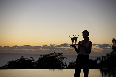 Waiter at the pool of Hotel Restaurant Le Rayon Vert in the evening light, Deshaies, Basse-Terre, Guadeloupe, Caribbean Sea, America