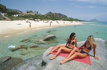Two young girls sitting on rocks on the beach, Costa Rei, Sardinia, Italy