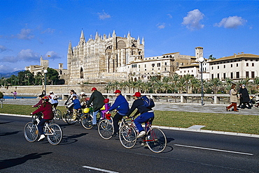 Group of cyclists, Cathedral La Seu, Palma Cathedral, Cathedral of Santa Maria of Palma, Palma de Mallorca, Mallorca, Spain