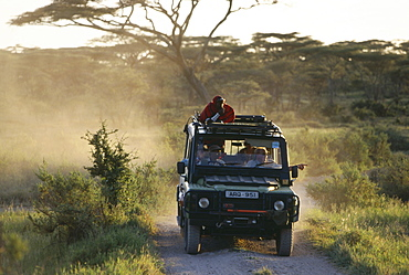 Tourists on a safari with massai tour guide, Serengeti, Tansania, East Africa