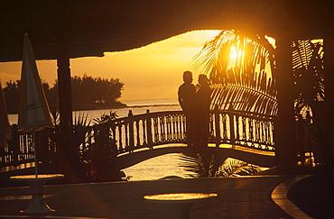 Couple on bridge against sunset, Royal Palm Hotel, Mauritius