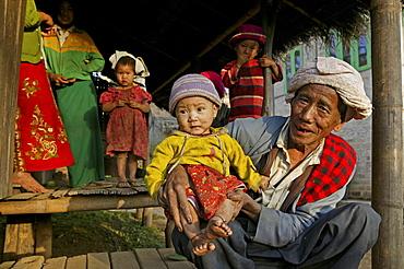 Portrait grandfather holding child, hill tribe, Burma, Myanmar