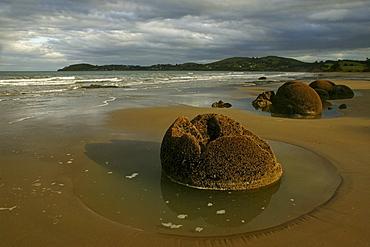 Moeraki boulders on the beach under clouded sky, South Island, New Zealand, Oceania