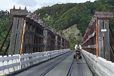 Cyclist on wooden bridge, traffic and railway sharing the narrow bridge, West Coast, South Island, New Zealand, Oceania