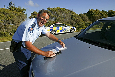 Policeman drawing a speeding ticket, Highway 6, West Coast, South Island, New Zealand, Oceania