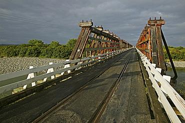 Wooden bridge under clouded sky, traffic and railway sharing the narrow bridge, West Coast, South Island, New Zealand, Oceania