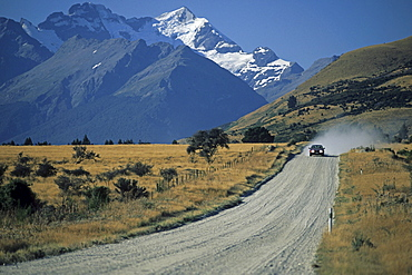 Country road with car in front of snowy mountains, Central Otago, South Island, New Zealand, Oceania