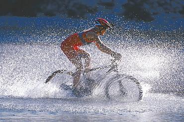 Woman cycling through water