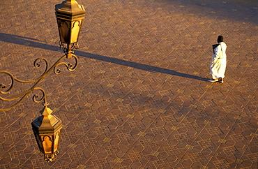 Man walking across Djemaa el Fna market square, Jemaa El Fna, Marrakesh, Morocco