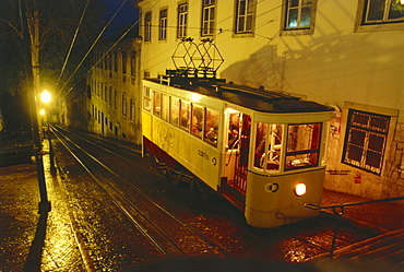 A streetcar going up a steep street at night, Elevador de Santa Justa, Lisbon, Portugal