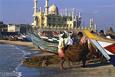 Fishermen and boats on the beach in front of mosque, Kovalam, Kerala, India