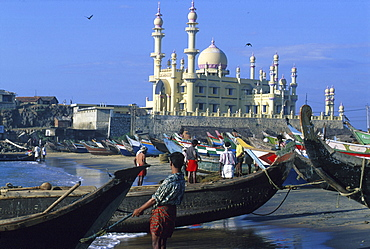 Fishermen and boats on the beach in front of mosque, Kovalam, Kerala, India, Asia