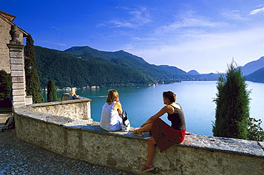 Two people enjoying view from church Santa Maria del Sasso, Morcote, Lago di Lugano, Ticino, Switzerland