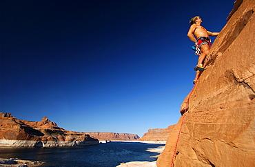 Man climbing up rock face, Lake Powell, Arizona, USA