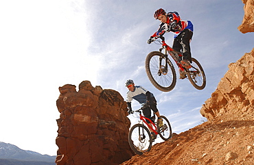 Two men on mountain bikes riding over rocks, Gooseberry Trail, Zion National Park, Springdale, Utah, USA