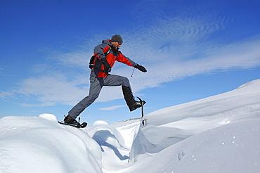 Man snowshoeing though deep snow, Ilulissat, Greenland