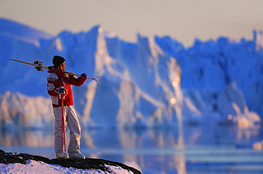 Woman carrying skis, admiring the view, Skiing, Ilulissat, Greenland