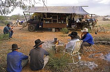 Stockmen sit around the cooks kitchen trailer, Kidman Station, South Australia, Australia