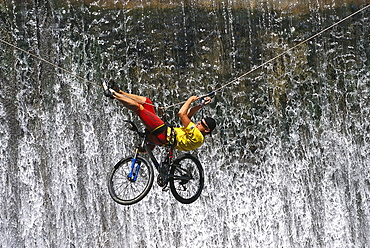 Mountain biker on a rope in front of waterfall