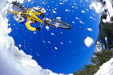 Mountainbiker jumping through snow, Alps, Austria