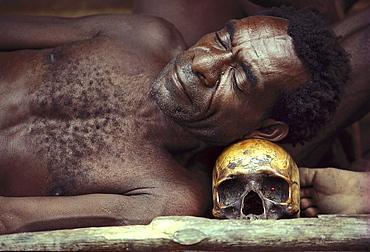 A man resting on a skull, Irian Jaya, Papua New Guinea