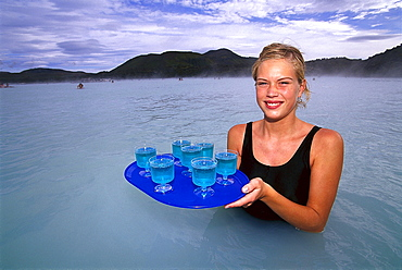 Young woman serving drinks in warm weater lake, Blue Lagoon, Grindavik, Iceland