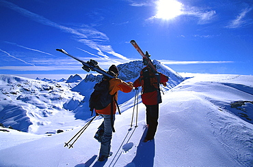 Two people with skis in snow covered scenery, Vorarlberg, Austria, Europe