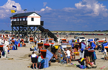 People on beach chairs in front of a stilted house on the beach, St. Peter Ording, Eiderstedt peninsula, Schleswig Holstein, Germany, Europe