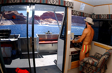 A man driving a boat on Lake Powell, Arizona, Utah, USA