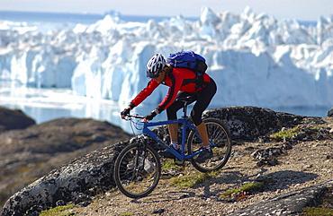 A man mountainbiking over rocks, Jakobshavn, Ilulissat, Greenland