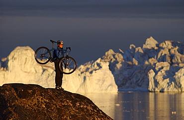 A Mountainbiker carrying her bike over rocks in the midnight sun, Jakobshavn, Ilulissat, Greenland