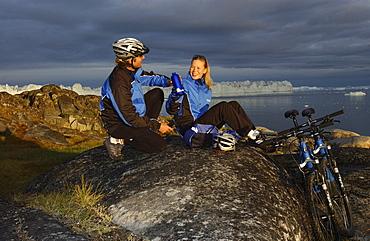 A couple having a break after mountainbiking, Jakobshavn, Ilulissat, Greenland