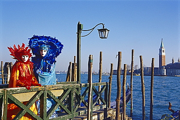 Masked people in disguise on a jetty in the sunlight, Venice, Italy, Europe