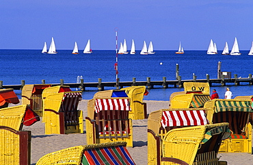 Beach chairs in the sunlight and sailing boats on the sea, Travemuende, Schleswig Holstein, Germany, Europe