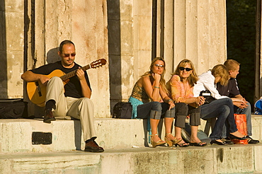 People sitting on stairs of Theseus Temple at Volksgarten, Vienna, Austria