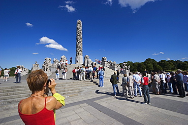 Tourist group on Monolith Plateau, granite sculptures by Gustav Vigeland in Vigeland Park, Oslo, Norway