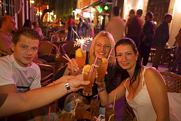 Young people toasting with drinks in an open-air bar at night, Kos-Town, Kos, Greece