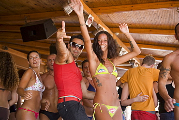 Young people dancing during a beach party at Tropicna Club, Paradise Beach, Mykonos, Greece