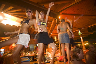 Young girls dancing a table during the full moon party, Tropicana Club, Paradise Beach, Mykonos, Greece
