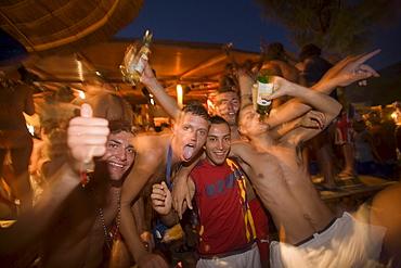 Men amusing during the Full Moon Party of the Tropicana Club, Paradise Beach, Mykonos, Greece