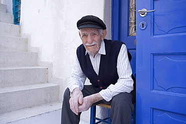A local old man sitting in front of a white house, Mykonos-Town, Mykonos, Greece