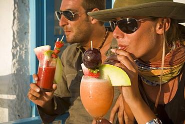 Couple enjoying the cocktail Sundowner in the Caprice Bar, Little Venice, Mykonos-Town, Mykonos, Greece
