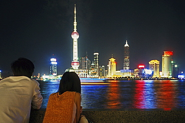Coupld looking onto skyline of Shanghai over Huangpu River, Shanghai, China